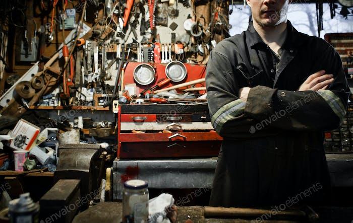 Arm gekreuzte Arbeiter in einem Schuppen und viele Werkzeuge hängen
