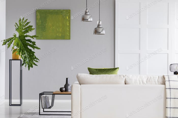 Lamps above white sofa in simple living room interior with green