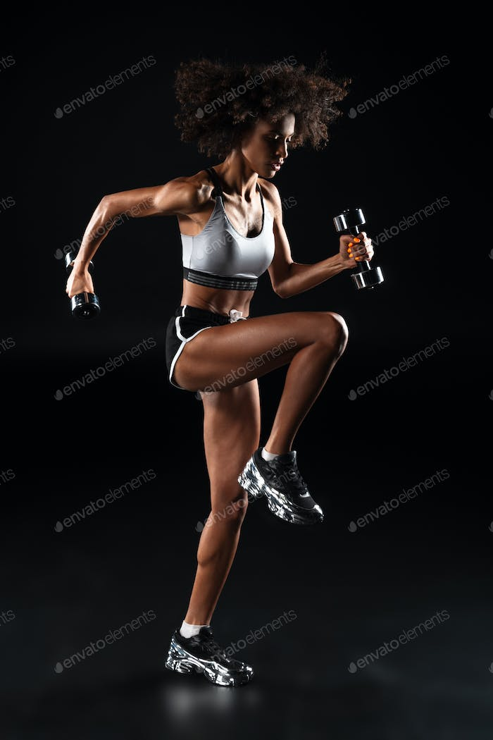 Image of african american sportswoman doing exercise with dumbbells