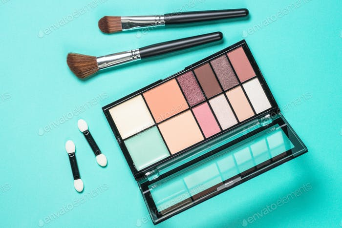 Eyeshadows and brushes at mint background