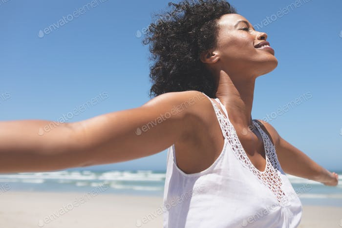 Young woman standing with open arm at beach on a sunny day