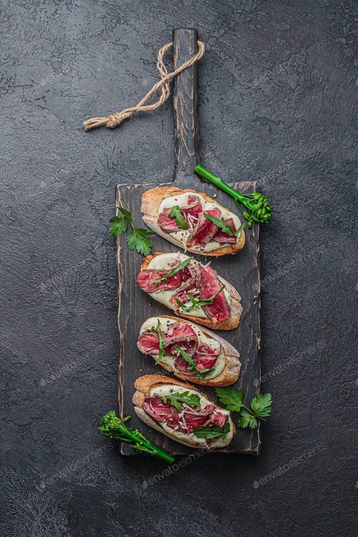 Bruschettas with beef on wooden board, flat lay