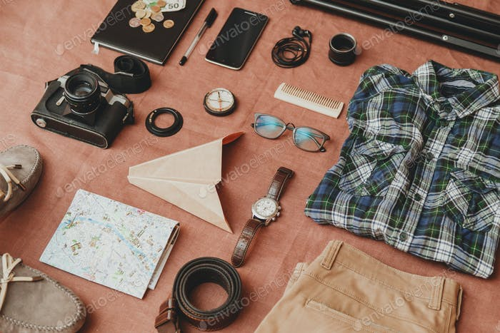 Trip concept - set of cool photography man stuff on linen cloth background