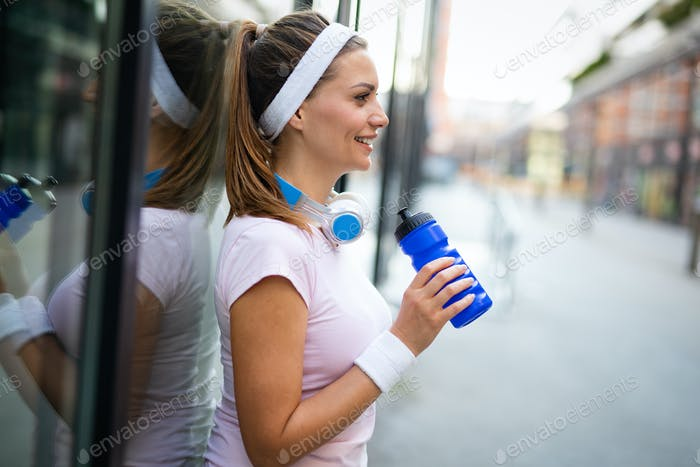 Beautiful sporty fit woman running and relaxing in city