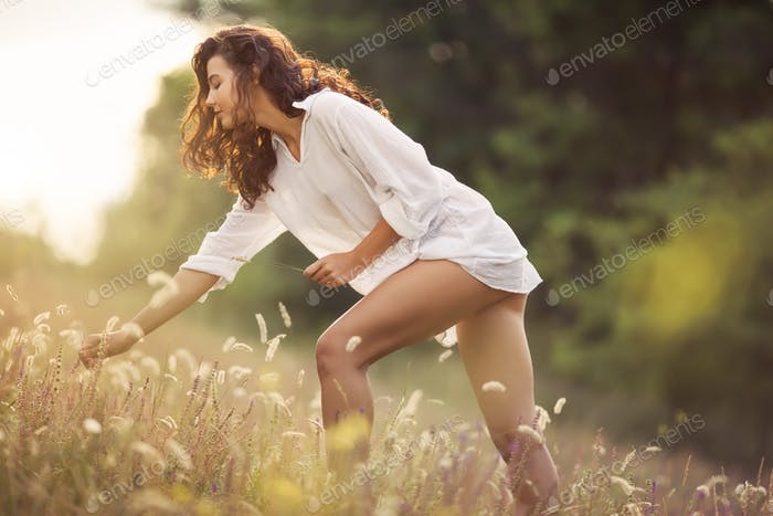 Natural beauty girl around flowers outdoor in freedom enjoyment concept