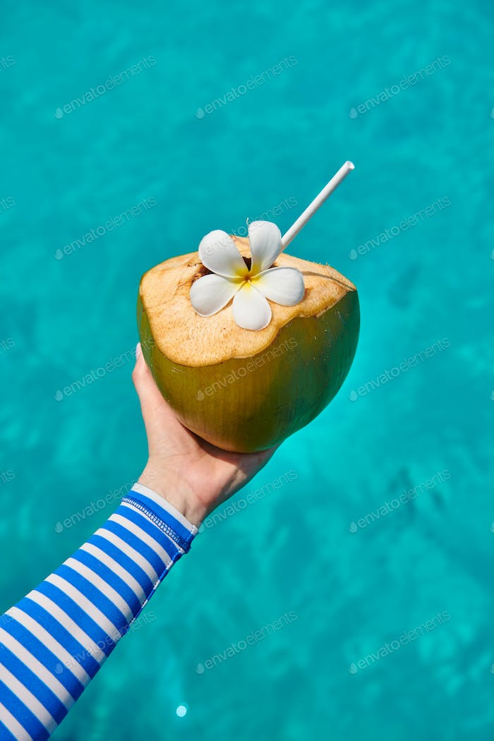 Coconut in hand over against turquoise sea
