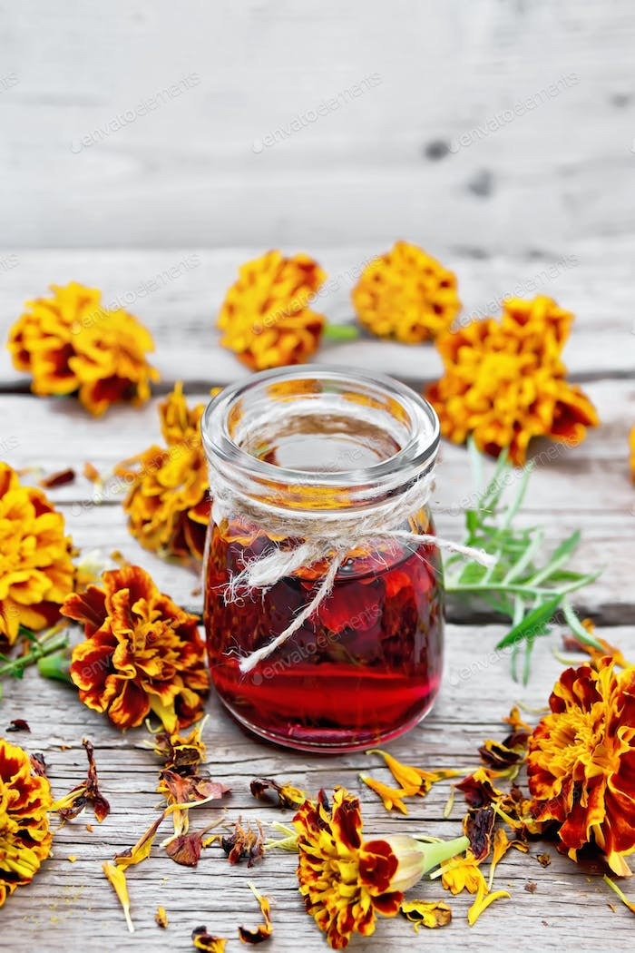 Alcohol tincture of marigolds in jar on old wooden board