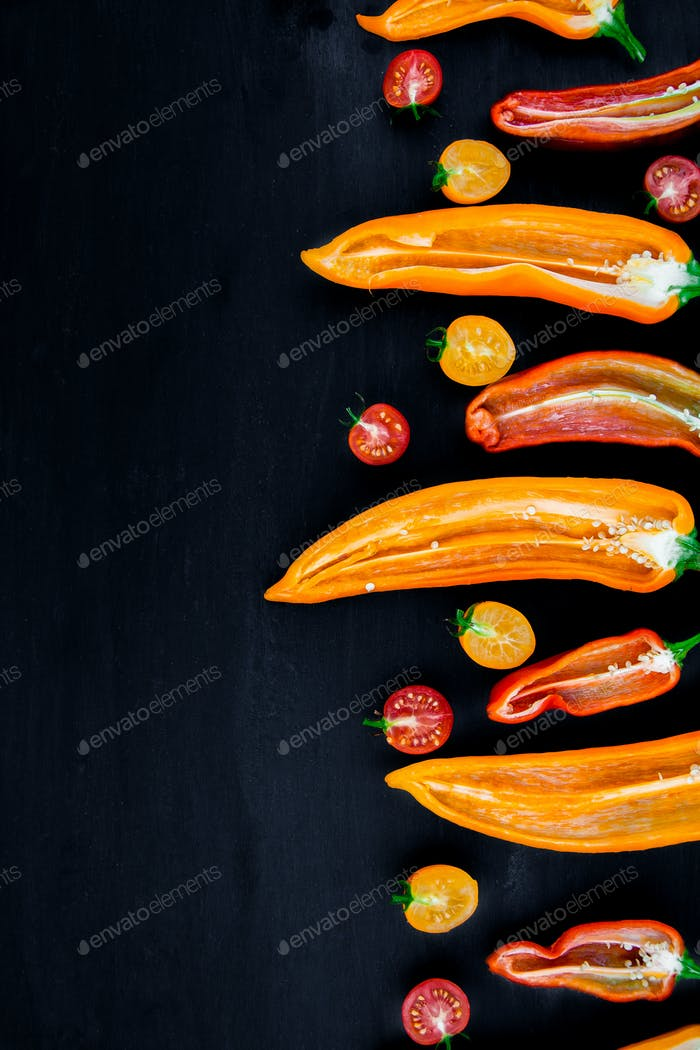 Mixed of half red and yellow pepper with a green branch near cherry tomato on black background.