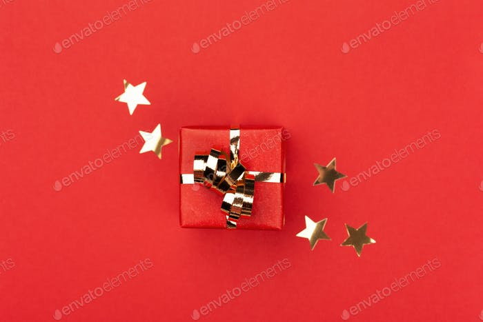 Red Gift Box on Red Background with Golden Confetti.