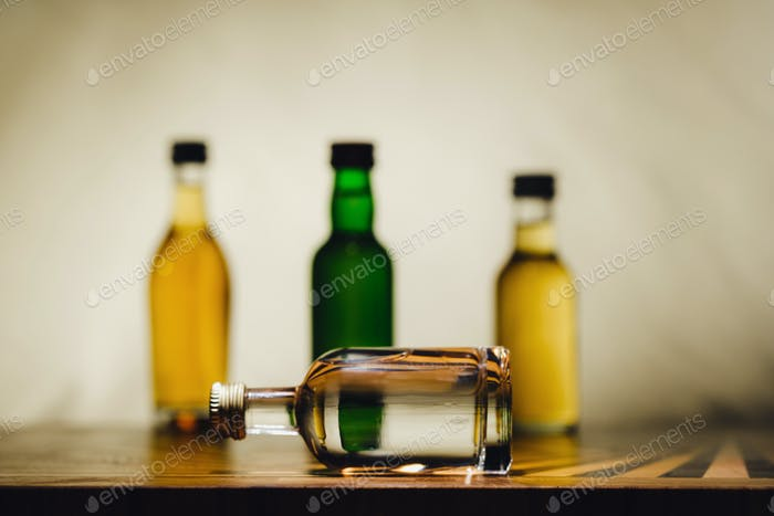 different alcohol bottles are on the table on a light background