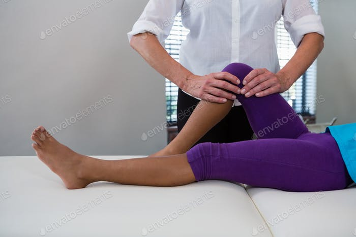 Physiotherapist giving leg massage to a girl patient