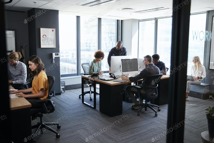 Young creative team working together at computers in a casual office, seen from doorway