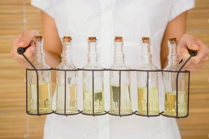 Close up view of woman holding bottles of oil massage