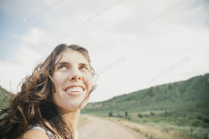 A young woman with windblown hair on a mountain road.