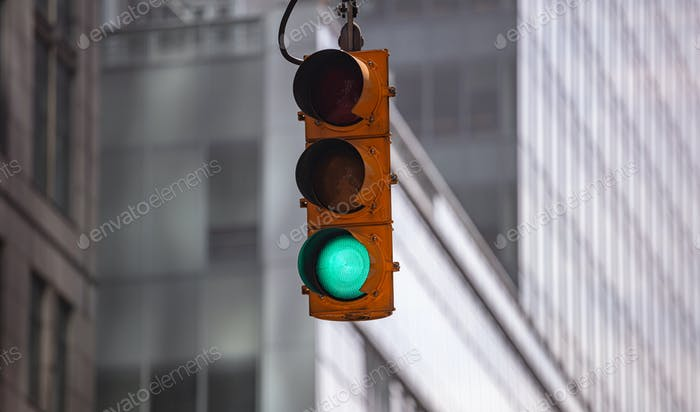 Green traffic lights for cars, blur office buildings background