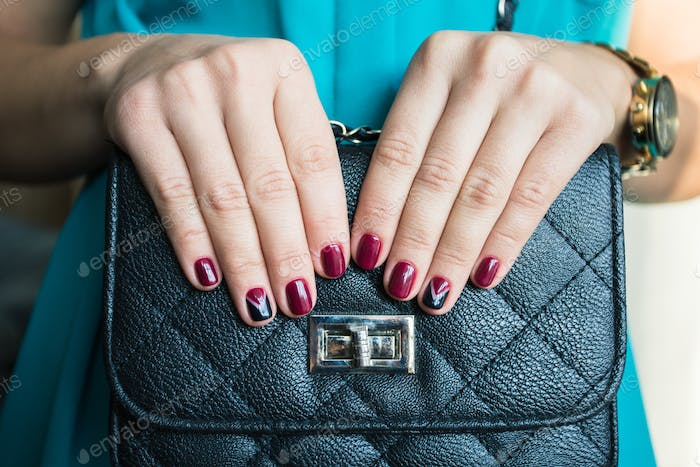 Female nails with red nail polish and a beautiful black handbag