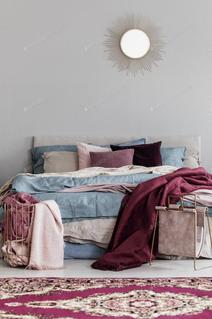 Colorful pillows and burgundy blanket on comfortable bed in fashionable bedroom interior