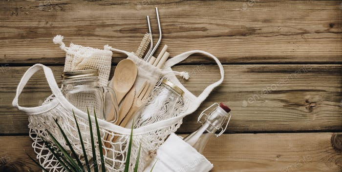 Mesh market bag with bamboo cutlery, reusable bottles and eco cotton bags on wooden background
