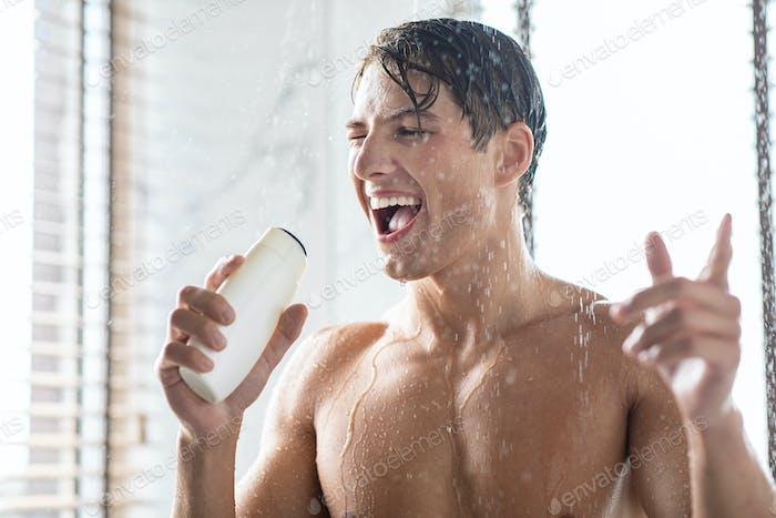 Junger Mann beim Körperwaschen singt in einer Shampoo-Flasche
