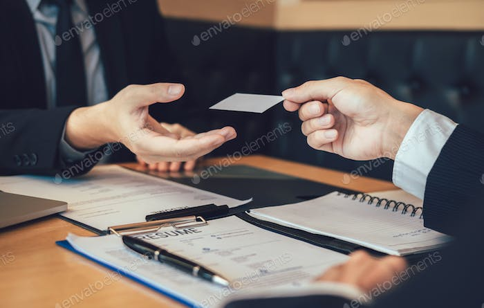 Employees submit business cards to job interviewers and interested in joining him contact