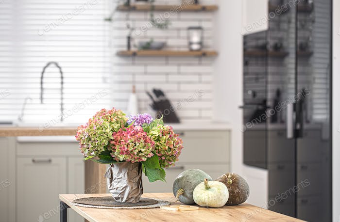 A bouquet of hydrangeas and pumpkins on the kitchen table as part of autumn home decor.