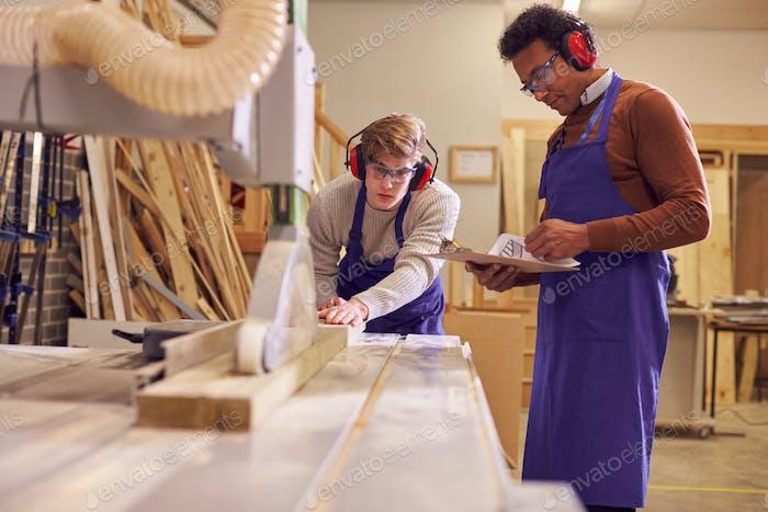 Tutor mit männlichen Zimmerei Student in Werkstatt Studieren Für Lehrlingsausbildung Am College Mit Bank Saw