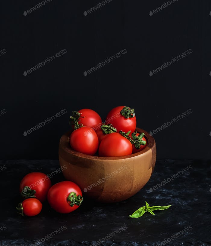 Ripe cherry-tomatoes in wooden bowl with basil leaves, spices and salt.