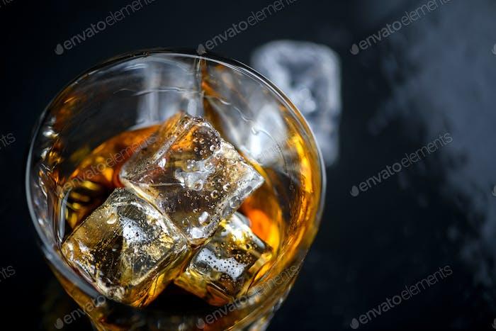 Glas Whisky mit Würfeleis auf schwarzem Hintergrund