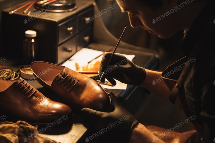 Cropped image of young concentrated man shoemaker