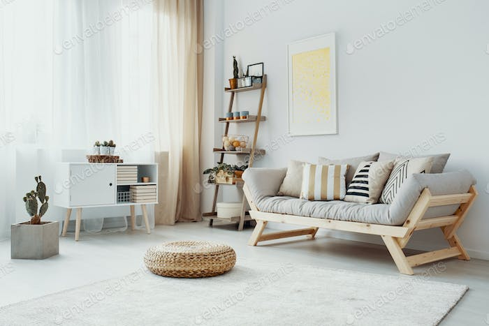 Pouf in front of wooden couch in bright living room interior wit