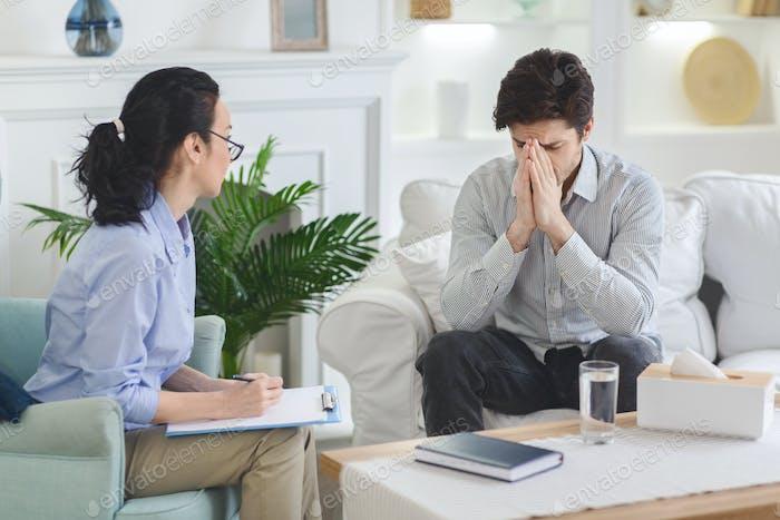 Depressed man emotionally speaking at psychotherapist session