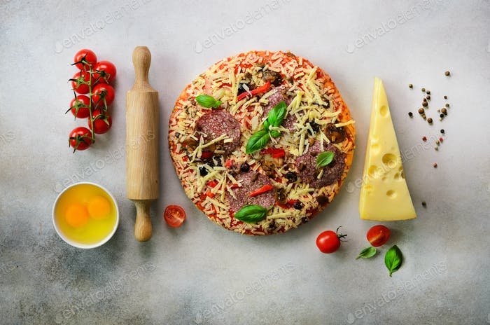 Food ingredients for italian pizza, cherry tomatoes, flour, cheese, basil, rolling pin, spices on