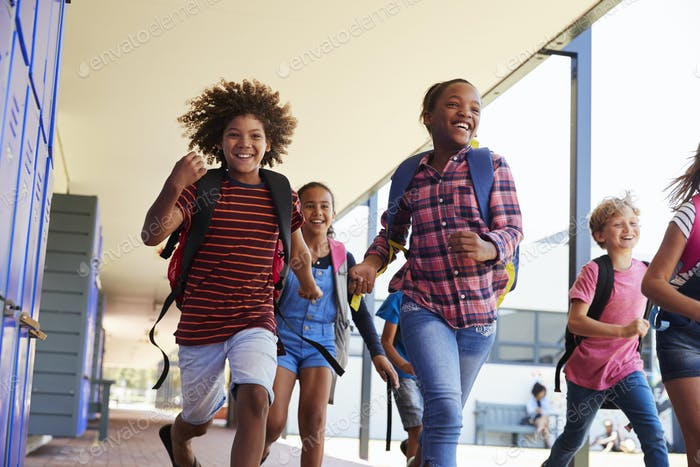 School kids running to camera in school hallway, close up