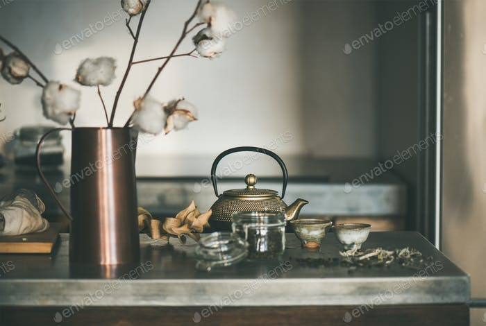 Golden teapot and cups full of tea on concrete counter