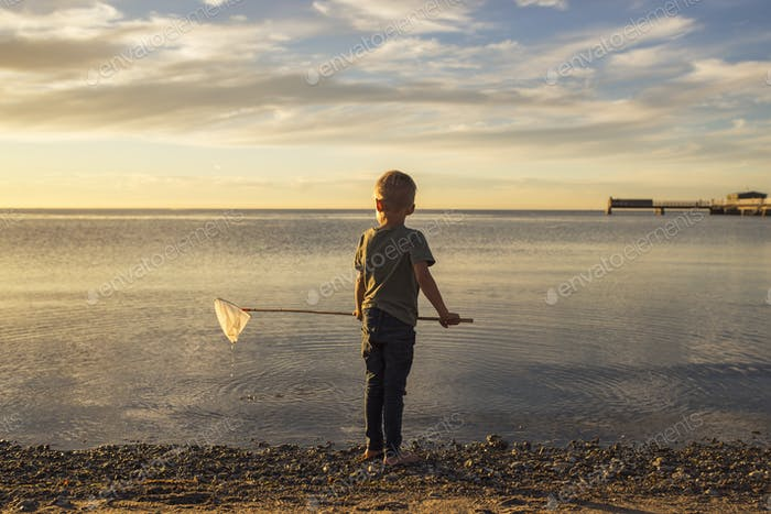 Boy (4-5) fishing in sea at sunset