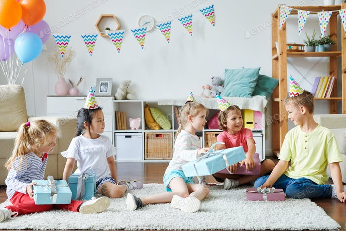 Group of happy adorable kids in birthday caps sitting on rug