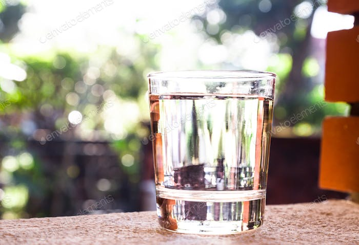 Refreshing water in transparent glass  against with greeneries b