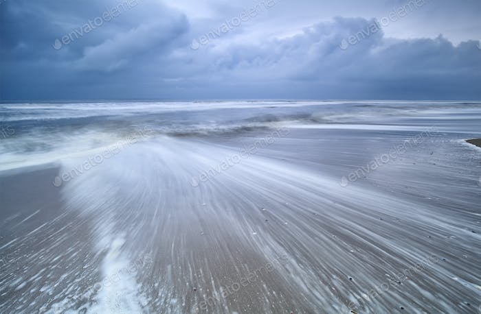 blurred waves on stormy sea coast