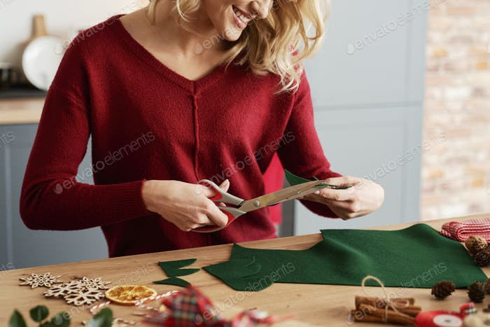 Happy woman cutting out Christmas decorations