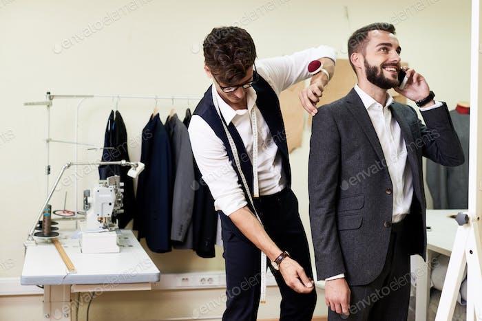 Handsome Tailor Measuring Customer