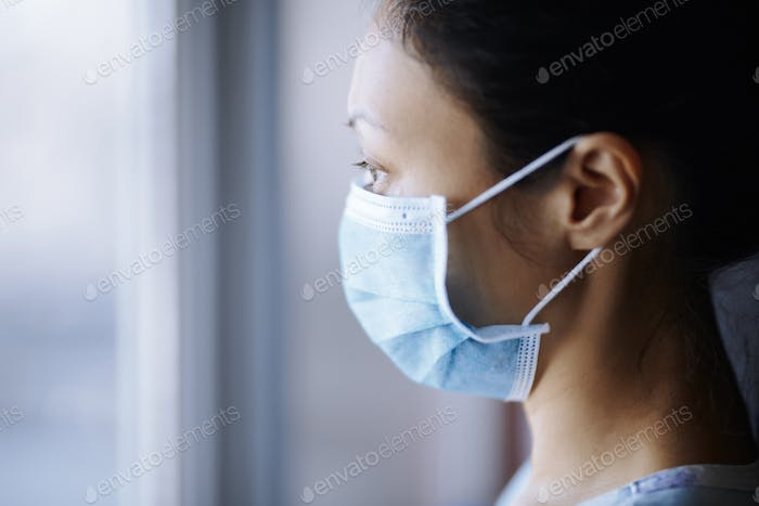 Woman staying at home and wearing protective surgical mask