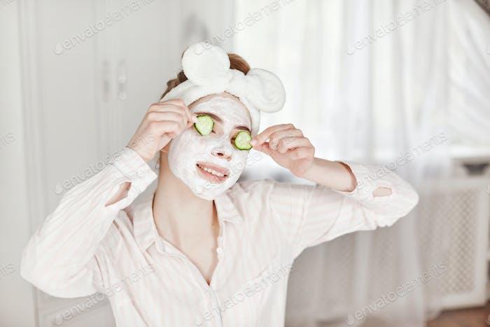 Una joven con una máscara en la cara y rodajas de pepino en los ojos.