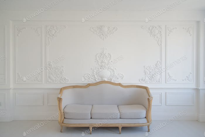 Living room with antique stylish light sofa on luxury white wall design bas-relief stucco mouldings
