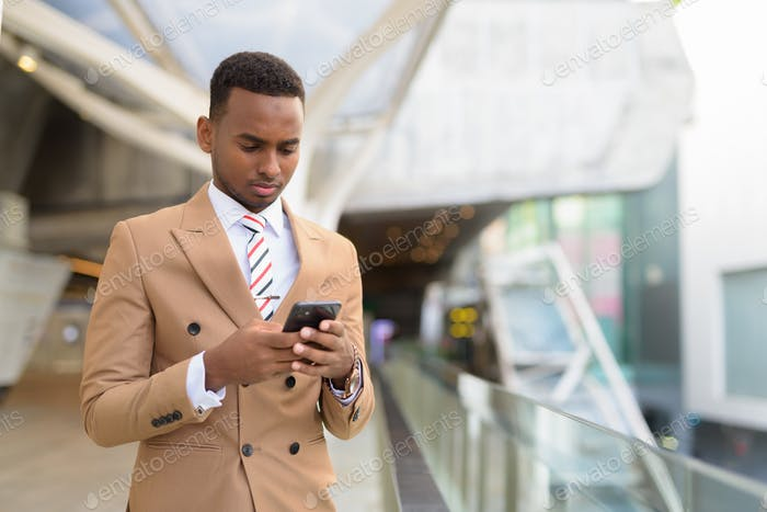 Young handsome African businessman using phone at the footbridge