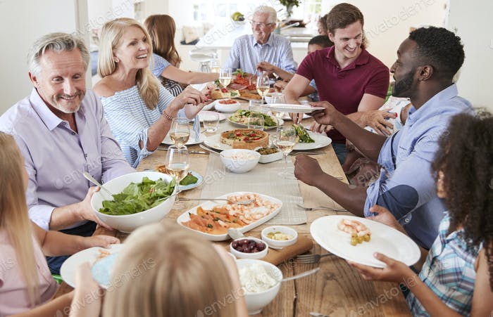 Group Of Multi-Generation Family And Friends Sitting Around Table And Enjoying Meal