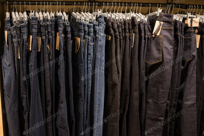 Jeans on clothes rail in clothing store at shopping mall.