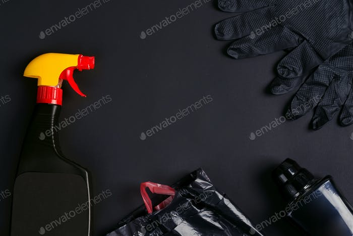 Plastic spray bottles, garbage bags and rubber gloves on a black background