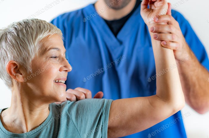 Therapist Checking Senior Woman's Arm