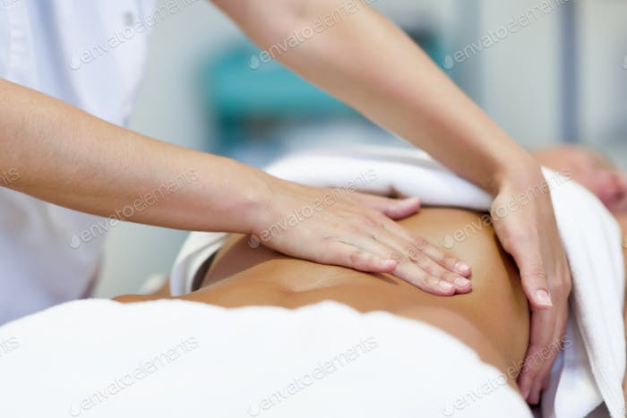 Woman having abdomen massage by professional osteopathy therapis