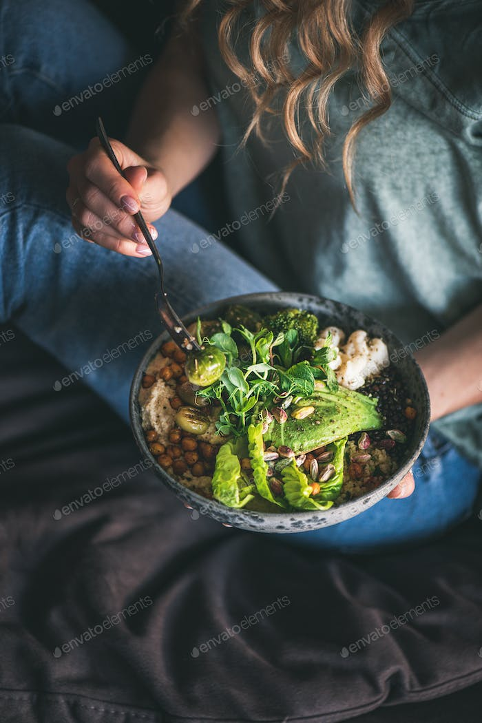 Woman sitting and eating vegan dish with himmus and avocado